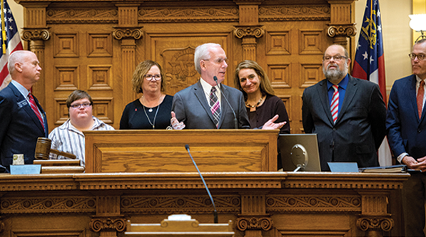 Rep. Tony Coelho (D - California) speaking about employment for people with disabilities in the Georgia Senate with (l to r) Hannah Hibben, Debbie Hibben, Elizabeth Appley and Eric Jacobson.